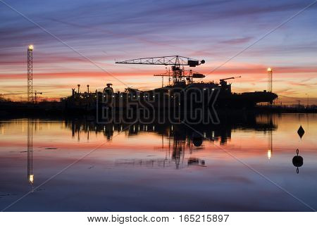 Spectucalar sunrise above a shipyard on the banks of the Dutch river merwede