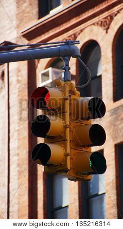 yellow traffic signaler hanging on a arm on a background of a brick wall with one red and one green light
