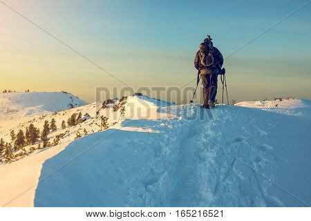 Man Hiker Going In The Mountains Through The Snow