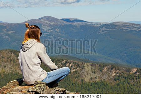 Young girl sitting on top of a mountain and looking at the beautiful mountain landscape