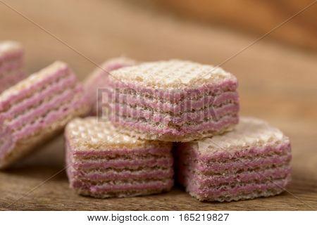 macro wafers stuffed with raspberry cream over wood