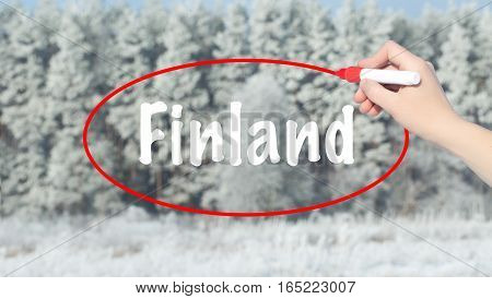 Woman Hand Writing Finland With A Marker Over Winter Forest.