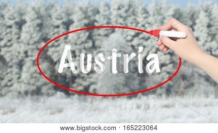 Woman Hand Writing Austria With A Marker Over Winter Forest.