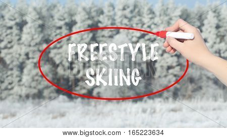 Woman Hand Writing Freestyle Skiing With Marker Over Winter Forest.