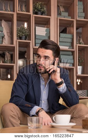 Young Man Sitting Sofa Indoors Coffee Cup Bar Espresso Phone Listening