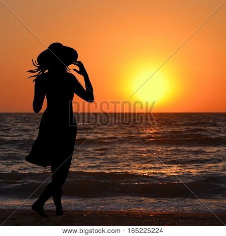 Woman with hat looking on the beach at sunrise