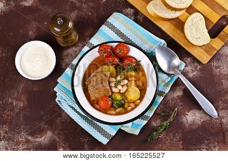 Meat soup with beans and vegetables. Selective focus.