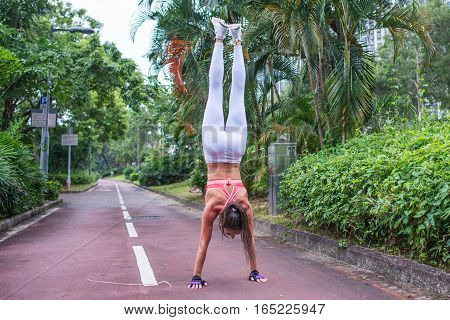 Rear view of fitness woman doing handstand exercise standing straight on outstretched arms on park lane in summer.