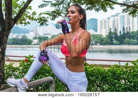 Sporty young female athlete taking a break after exercising or running, standing and drinking water from a bottle in park on summer day with river and city buildings behind her back.