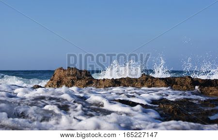 White foamy water and brown rocks under a blue clear sky