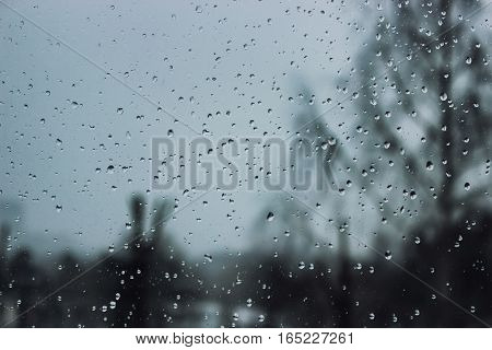 Soft and blur conception. Drops of water on the window in winter season. Background with drop of water closeup