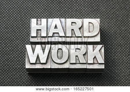 hard work phrase made from metallic letterpress blocks on black perforated surface
