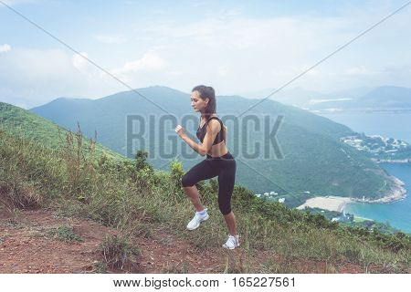 Fit female jogger exercising, running uphill with sea and mountains in background.