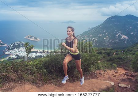 Young fit tanned woman trail running up the steps carved into the hillside with mountains, sea, islands and cloudy sky in background.
