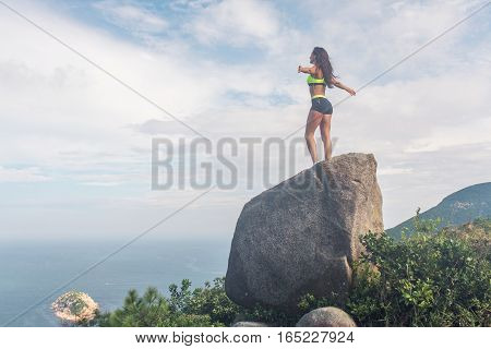 Rear view of inspired sportswoman standing on a rock in the mountains with her arms outstretched admiring the view of cloudy sky and sea in summer.