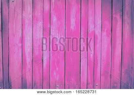 pink, violet old wooden fence. wood palisade background. planks texture