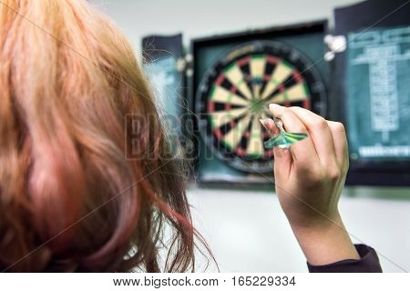 Closeup of young woman's head and hand throwing a dart