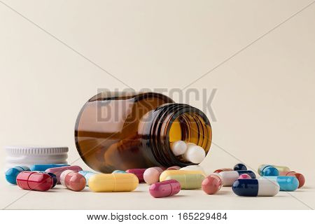 Bottle of pills from the brown glass and heap of colorful capsules