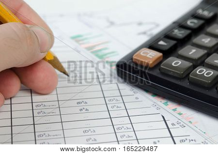 Hand with pencil making notes in the accounting lists
