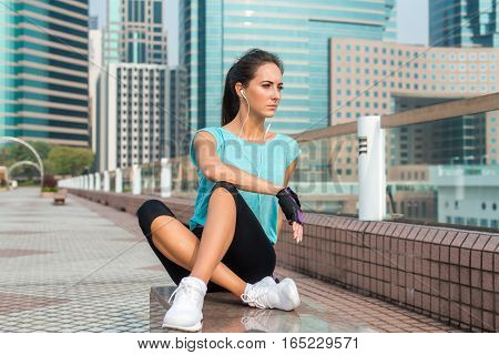 Female athlete tired after running or training resting on bench. Fit young woman relaxing and listening to music