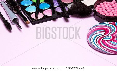 Decorative cosmetics for festive party make up. Blush, color glitter eyeshadow, liquid eyeliner, mascara, brushes with lollipop. Copy space
