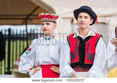 Silver Spring, USA - September 17, 2016: Two Ukraina School of Dance Ensemble teens dressed in traditional red Ukrainian embroidered costume clothes preparing to dance at 14th Washington Ukrainian festival