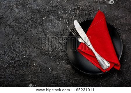 Fork, knife and red napkin and black plate. On dark table background.