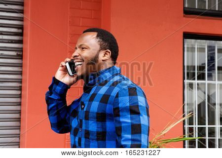 Young African American Man Walking And Talking On Mobile Phone