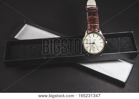 men watch in a gift box on black background
