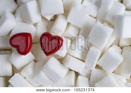 Cubes of white sugar with two red hearts as background. Close up. Top view