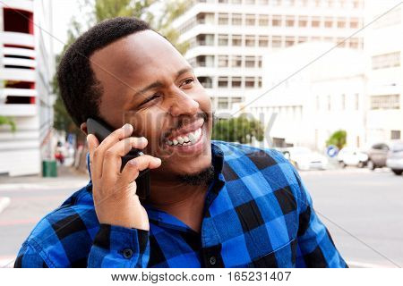 Smiling Young African Man Talking On Cellphone In The City