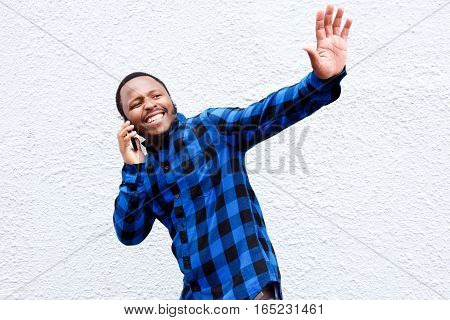 Young Man Talking On Cellphone And Waving Hand