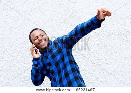 Cheerful Man Talking On Cellphone With Thumbs Up Hand Sign