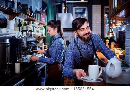 Bartender waiter with a kettle and mug of coffee tea working in the workplace bar, cafe.