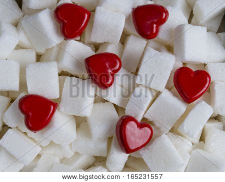 Sugar cubes with two red hearts as background. Close up. Top view
