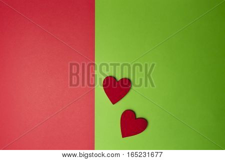 Two hearts on greenery and red colored paper background. Minimal style. Flat lay. Top view. Copy space for text