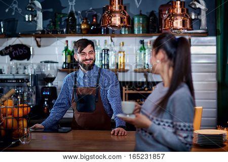 Bartender, barista and customer in the cafe bar restaurant.