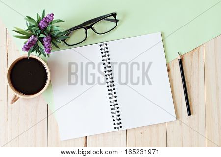 Still life, business, office supplies, education or vintage concept : Top view of working desk with blank notebook with pencil, coffee cup, eyeglasses and plant on wooden background