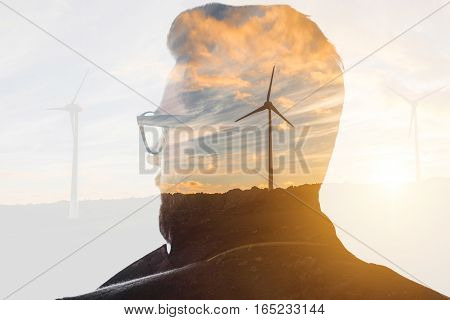 Double exposure portrait of a businessman thinking about renewable electricity combinated with sunset landscape and winmills