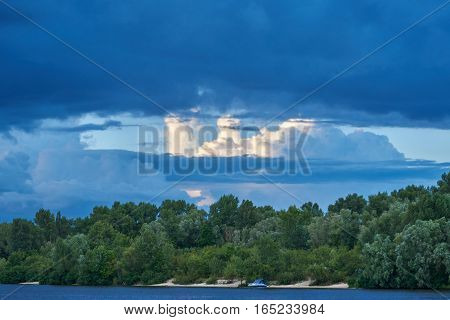 Landscape. The sandy coast of the river overgrown with deciduous forest. In the sky cumulonimbus