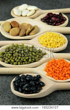Dried black red broad beans and and red and yellow lentils on wooden spoons on a dark table.