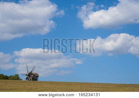 Landscape with a windmill against the blue sky with cumulus clouds. Background
