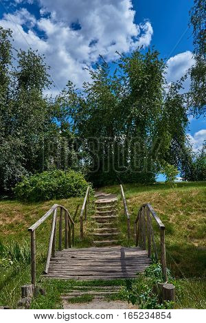 Landscape with a wooden bridge stairs trees against the blue sky with cumulus clouds