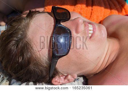 beautiful woman lying in sunglasses on the beach