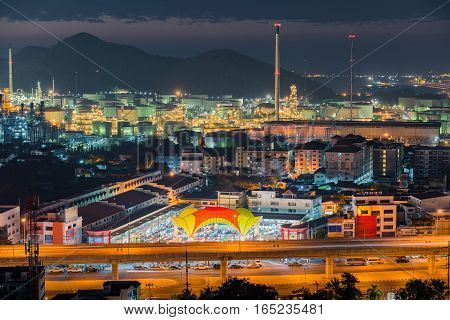 Luminosity of oil refinery plant and urban city at night scene.
