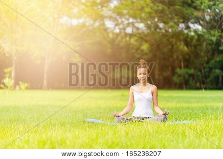 Asian girl do yoga meditation at the park in the morning with sunlight