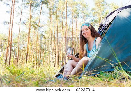 Guy sitting near the tent in the forest drinking tea and smiling