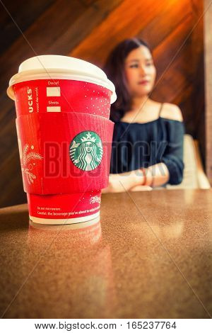 Bangkok Thailand-December 25 : Starbucks hot coffee on table with lady background on 25 December 2016 at Starbucks shop Bangkok Thailand.