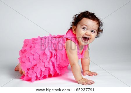 A very happy baby girl in a pink layered dress crawls and laughs. She is is bright happy and expressive with four teeth. Her eyes are looking up and to the side.