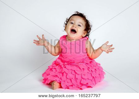 An adorable baby girl sits in a pink frilly layered dress with an excited surprise expression. She has her hands out to the side and head tilted back.